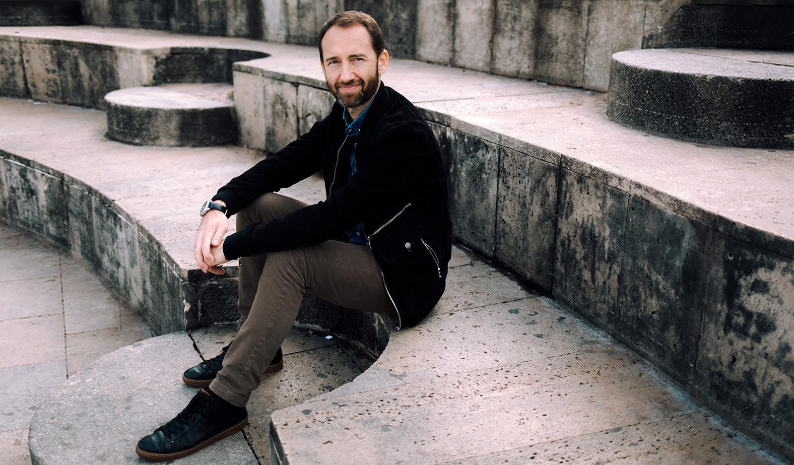 Raphael Alix assis sur des marches